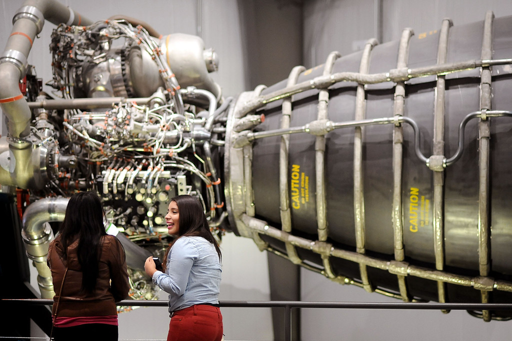 ". Visitors enjoy themselves while viewing a space shuttle main engine at the California Science Center in Los Angeles, CA October 11, 2013.   In honor of Endeavour\'s 1st year in Los Angeles, the museum is holding ""Endeavour Fest\"" beginning today (Oct. 11) and running through Sunday with special exhibits and astronaut guest speakers scheduled.(Andy Holzman/Los Angeles Daily News)"