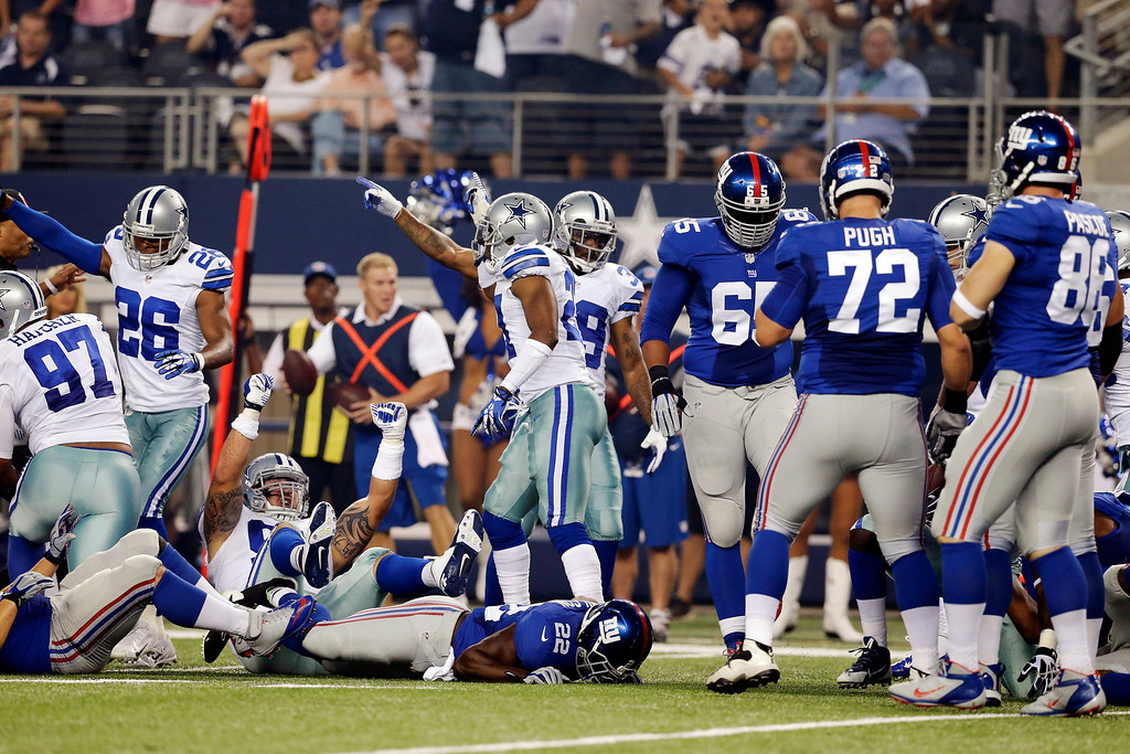 . The Dallas Cowboys celebrate a fumble by New York Giants running back David Wilson (22) during the first half of an NFL football game, Sunday, Sept. 8, 2013, in Arlington, Texas. (AP Photo/LM Otero)