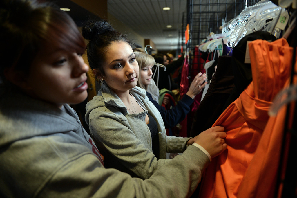 """. COMMERCE CITY, CO. - MARCH 16: Alicia Chavez, left, and Mickaelas Mader, both seniors at North High School, look through the selection at the Prom Dress Exchange Corp. event in Commerce City, CO March 16, 2013. With a valid student ID and a suggested $10 donation, teenage girls could chose from 1,356 donated dresses that lined a long hallway at Dick�s Sporting Goods Park. Chavez said prom is expensive, \""""this is awesome, we can spend our money on other stuff.\"""" (Photo By Craig F. Walker/The Denver Post)"""