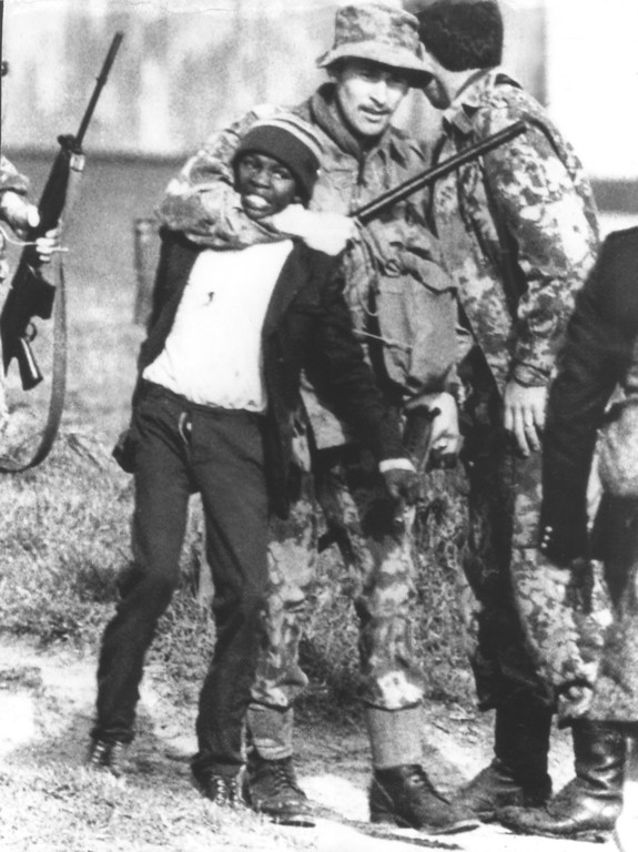 . A South African policeman collars a black student during rioting in Guguletu, near Cape Town, November 24, 1976. Deaths and mass detentions of black leaders by security police in outbreaks of violence since June have raised visions of a racial armageddon in South Africa, where four millions of white rule the destiny of 18 million blacks, 2.3 million coloreds, persons of mixed race, and 709,000 Asians. (AP Photo)