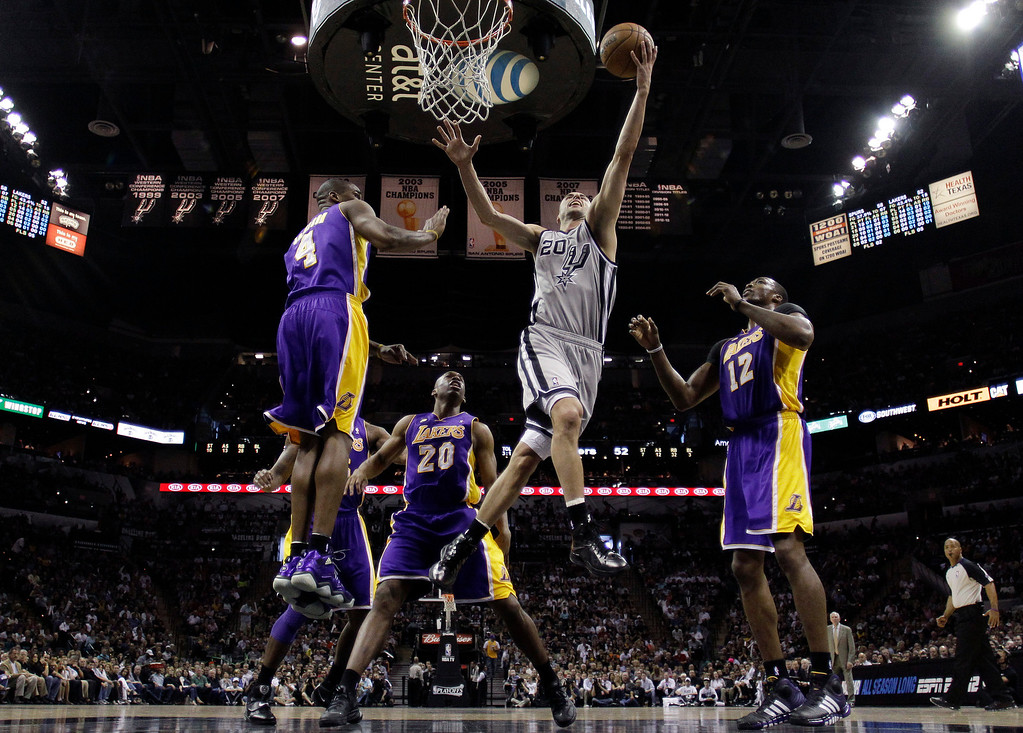 . San Antonio Spurs\' Manu Ginobili, front center, of Argentina, drives to the basket between Los Angeles Lakers\' Antawn Jamison (4), Jodie Meeks (20) and Dwight Howard (12) during the second half of Game 1 of their first-round NBA basketball playoff series on Sunday, April 21, 2013, in San Antonio. San Antonio won 91-79. (AP Photo/Eric Gay)