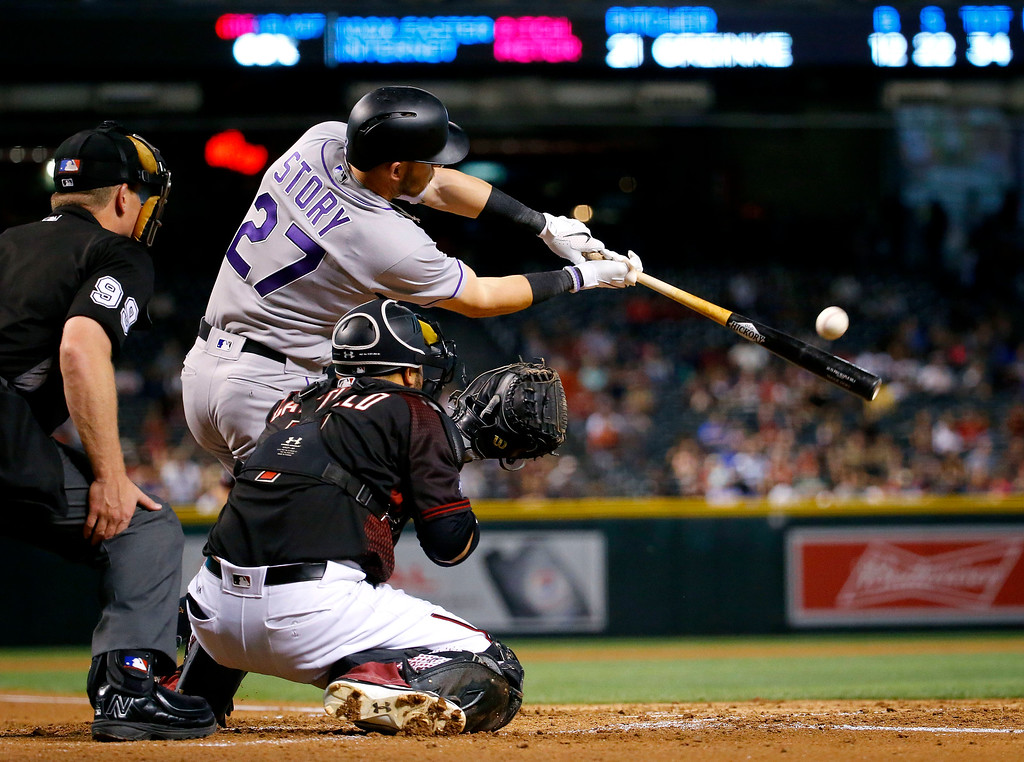 . Colorado Rockies\' Trevor Story (27) connects for an RBI double as Arizona Diamondbacks catcher Welington Castillo (7) catches during the third inning of a baseball game, Saturday, April 30, 2016, in Phoenix. (AP Photo/Matt York)