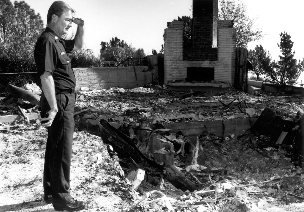 . Fire Capt. Donald Pierpont examines the surrounding vegetation which may have contributed to how a home did not survive the Malibu fire.  (11/10/93) Los Angeles Daily News
