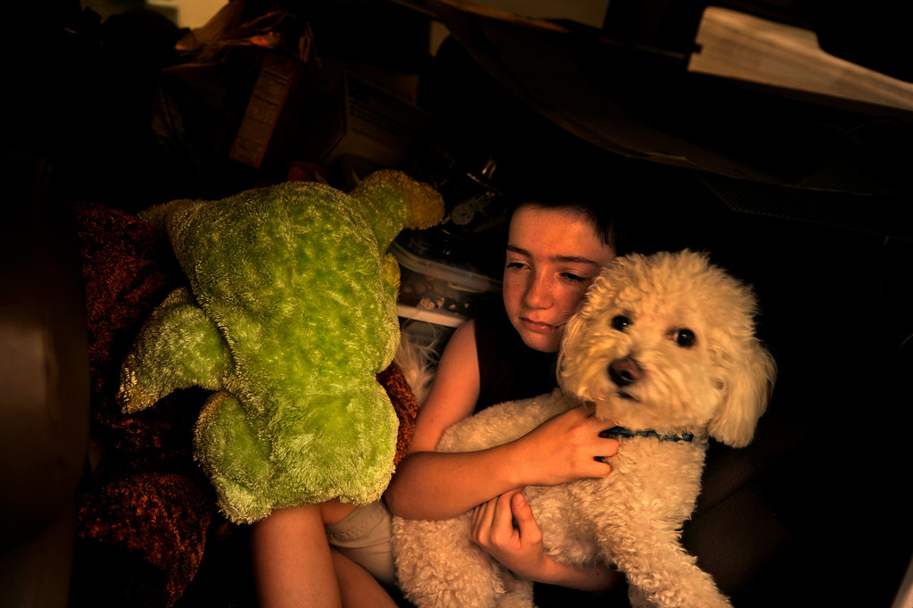. Taylor Salamon, 11, holds on to his dog as they pile in the back seat, Tuesday June 26, 2012, as his family rushes to leave their home in the path of Waldo Canyon Fire in Colorado Spring. RJ Sangosti, The Denver Post