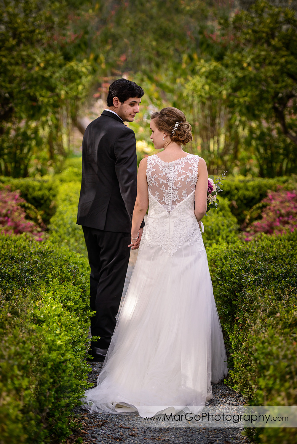 full body portrait of bride and groom walking down green aisle during bridal session at Shinn Historical Park and Arboretum in Fremont