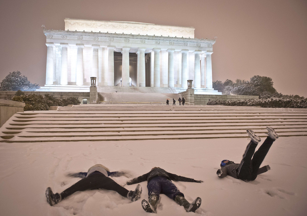 . Young people make \'snow angel\' shapes in the snow in front of the Lincoln Memorial as a heavy snow storm hits Washington D.C. on February 13, 2014. The eastern US, in the grips of one of the most brutal winters in recent memory, braced for what forecasters warned could be the worst broadside yet -- a massive storm with the season\'s heaviest snowfall. AFP PHOTO / MLADEN ANTONOV/AFP/Getty Images