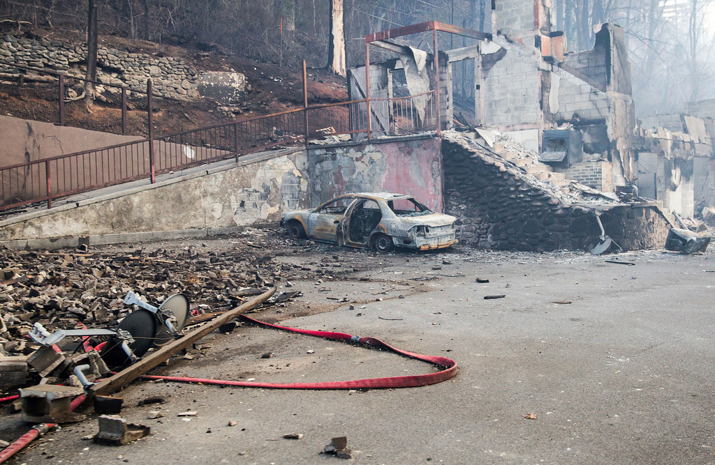 . A scorched vehicle sits next to a burned out building in Gatlinburg, Tenn., Tuesday, Nov. 29, 2016. The fatal fires swept over the tourist town the night before, causing widespread damage. Thousands of people raced through a hell-like landscape to escape wildfires that killed several people and destroyed hundreds of homes in the Great Smoky Mountains. (AP Photo/Erik Schelzig)