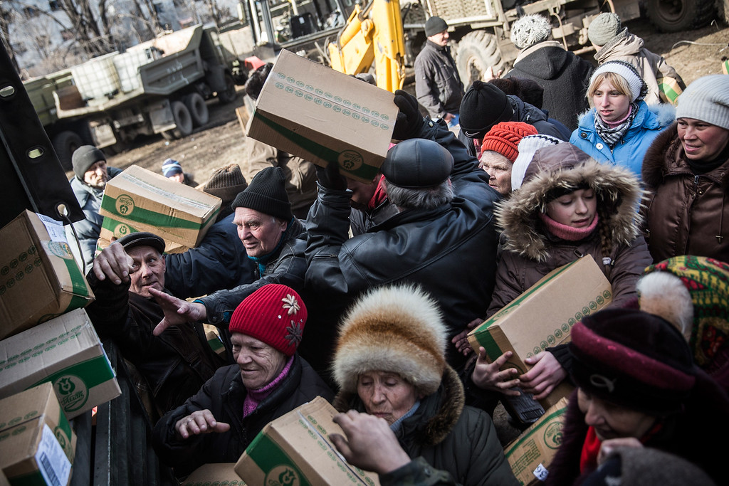 . DEBALTSEVE, UKRAINE - FEBRUARY 25:  Russian backed rebels hand out boxes of food to civilians on February 25, 2015 in Debaltseve, Ukraine. After approximately one month of fighting, Russian backed rebels successfully forced Ukrainian troops to withdraw from the town of 100,00 people on February 18. Only approximately 11,000 civilians remain in the town. Debaltseve is considered an asset to both Ukrainians and the rebels due to the railway station and it\'s connection to other eastern Ukranian towns.  (Photo by Andrew Burton/Getty Images)