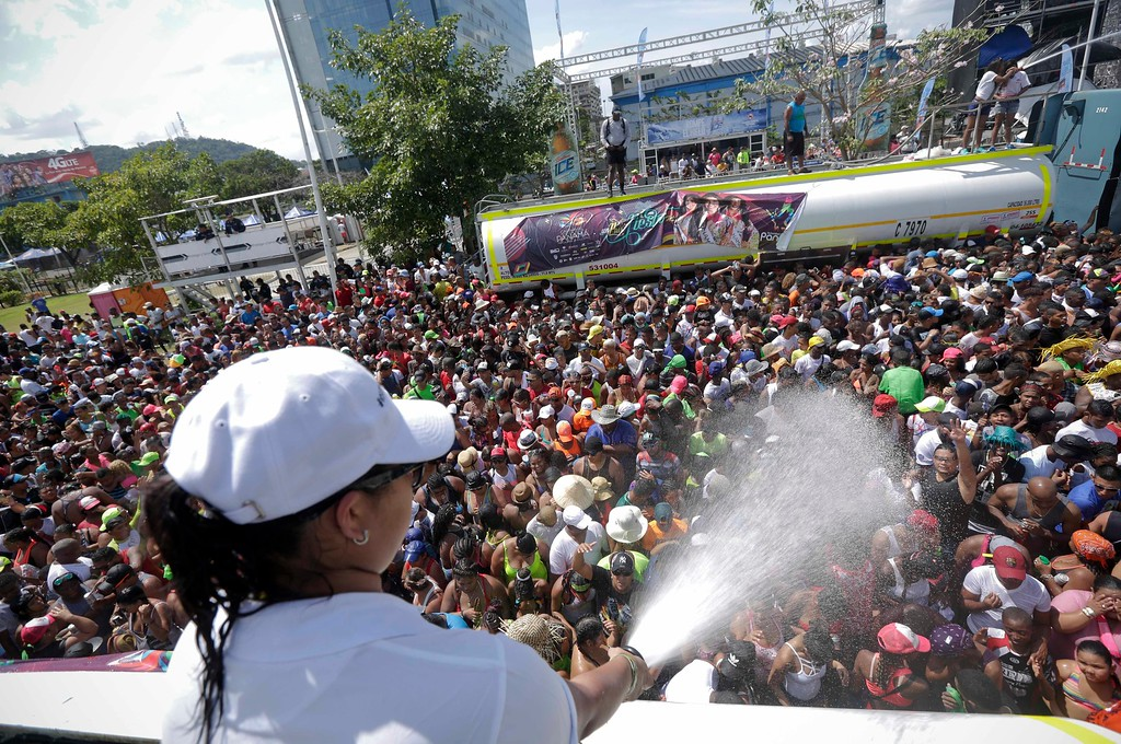 . Revelers dance as they are sprayed with water from a tanker truck during the carnival celebrations in Panama City, Monday, Feb. 27, 2017. Carnival is celebrated throughout the country every year for four days before Ash Wednesday. (AP Photo/Arnulfo Franco)