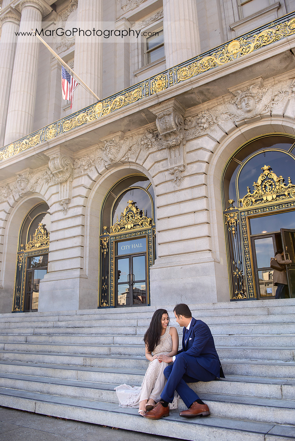 woman in beige dress and man in navy blue suit sitting on stairs outside of San Francisco City Hall