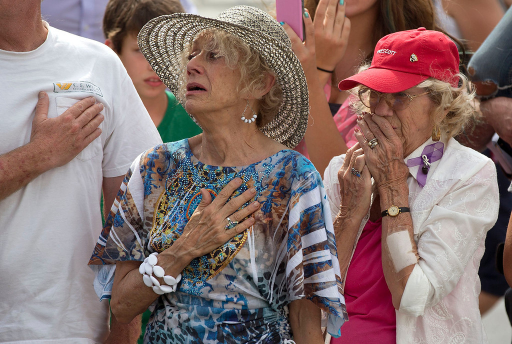 . Two women react as as 19 hearses slowly roll by, Sunday, July 7, 2013 in downtown Prescott, Ariz., carrying the 19 Granite Mountain Hotshot firefighters killed a week ago by an out-of-control blaze near Yarnell, Ariz. The nearly five-hour-long procession began near the state Capitol in Phoenix, went through the town where the Granite Mountain Hotshots were killed and ended in the mountain community of Prescott, where they lived and will be laid to rest this week.(AP Photo/Julie Jacobson)