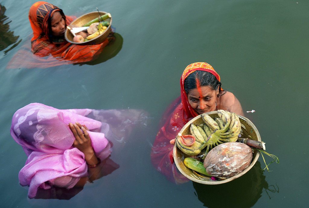. Indian Hindu devotees perform rituals as they worship the setting sun during Chhath Puja while standing in a water body in Kolkata on November 8, 2013.  Devotees pay obeisance to both the rising and the setting sun during the Chhath festival when people express their thanks and seek the blessings of the forces of nature, mainly the Sun and the River.   AFP PHOTO/Dibyangshu SARKAR/AFP/Getty Images