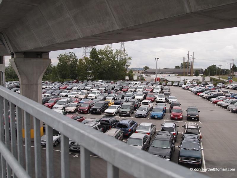 Ironic, big parking lot, full, under the public transit bridge.