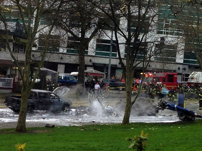 . Emergency personnel respond to the scene of a helicopter crash outside the KOMO-TV studios near the space needle in Seattle on Tuesday, March 18, 2014. The station says the helicopter was apparently coming in for a landing on its rooftop Tuesday morning when it possibly hit the side of the building and went down, hitting several vehicles on Broad Street. Two people inside the helicopter were killed (AP Photo/The Seattle Times, Mike Siegel)