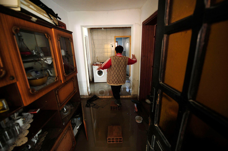 . A woman walks through her flooded home to salvage belongings in Sveti Nikole, 60 km (37 miles) northeast from capital Skopje February 26, 2013. One man was drowned and several hundred homes in Macedonia were flooded on Tuesday as two days of heavy rain drenched farmland and caused power outages in the Balkan country, authorities said.  REUTERS/Ognen Teofilovski