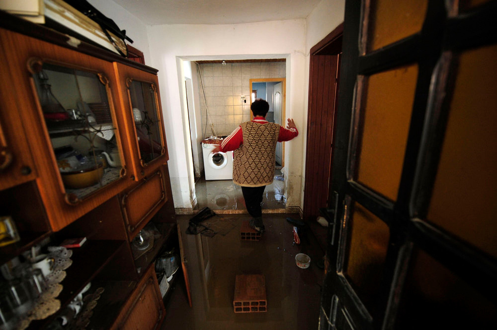 Description of . A woman walks through her flooded home to salvage belongings in Sveti Nikole, 60 km (37 miles) northeast from capital Skopje February 26, 2013. One man was drowned and several hundred homes in Macedonia were flooded on Tuesday as two days of heavy rain drenched farmland and caused power outages in the Balkan country, authorities said.  REUTERS/Ognen Teofilovski