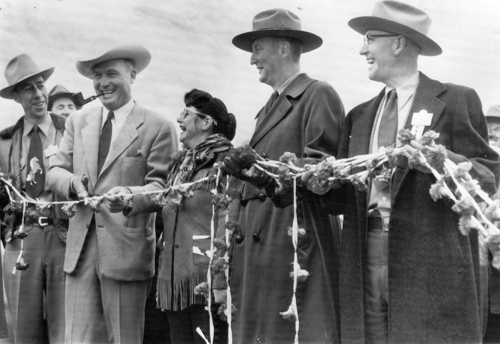 . Participating in the 1951 Trail Ridge Road Ribbon-Cutting ceremony opening the road are, left to right Ronald Brodie, mayor of Estes Park; Gov. Thornton, cutting the �rope� of Colorado carnations; Shirley Yahai of Los Angeles, Calif., radio station KFEL�s �Queen for a Day�; David Canfield, superintendent of Rocky Mountain National Park, and Jake Pettingell, president of the Grand Lake Chamber of Commerce. (Floyd H. McCall/The Denver Post)