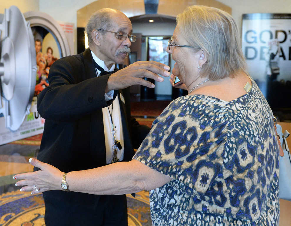 . Al Harris, floor manager of the Krikorian Premier Theatre, hugs Jacqui Byron of San Bernardino, Thursday, in Redlands,Ca., Feb. 13, 2014. Harris has become a local icon collecting tickets and giving high fives to moviegoers since being hired by Krikorian in 1992.  (John Valenzuela/Photographer)