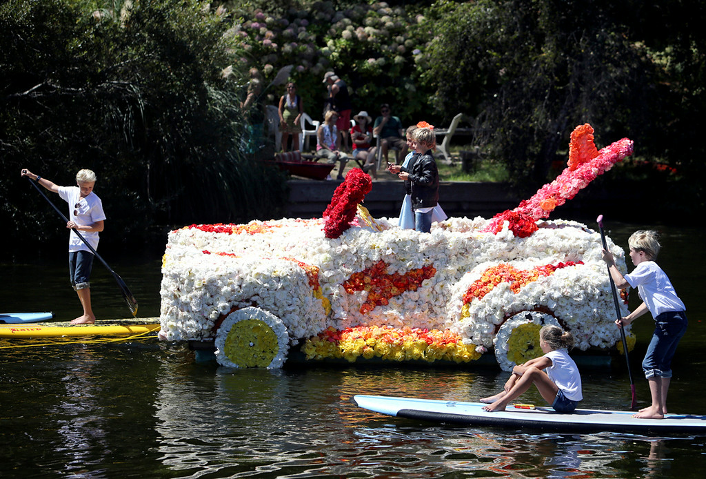 . The Grease float carries two young children across Soquel Creek on Sunday during the annual Begonia Festival Nautical Parade. (Kevin Johnson -- Santa Cruz Sentinel)