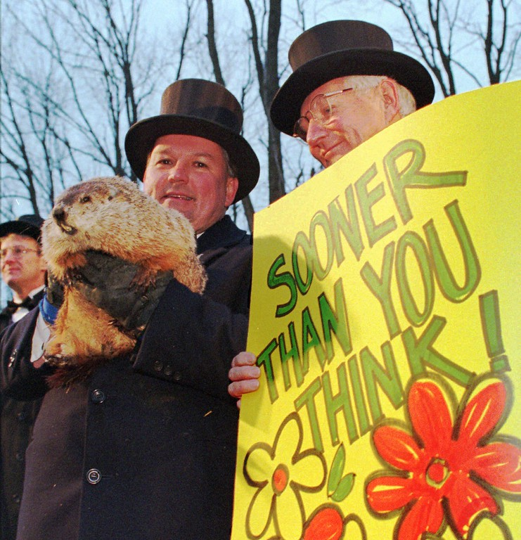 . Punxsutawney Phil is held by handler Bill Deeley, left, as Deeley tells Groundhog Club president Bud Dunkel that Phil failed to see his shadow upon emerging from his burrow on Gobbler\'s Knob in Punxsutawney, Pa., Sunday, Feb. 2, 1997, indicating spring is right around the corner. Legend has it that if the groundhog sees his shadow, six more weeks of winter lay ahead. (AP Photo/Gene J. Puskar)