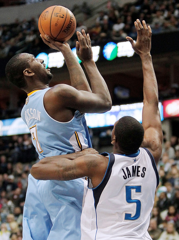 . Denver Nuggets forward J.J. Hickson (7) attempts a shot as Dallas Mavericks Bernard James (5) defends during the first half of an NBA basketball game Monday, Nov. 25, 2013, in Dallas. (AP Photo/Brandon Wade)