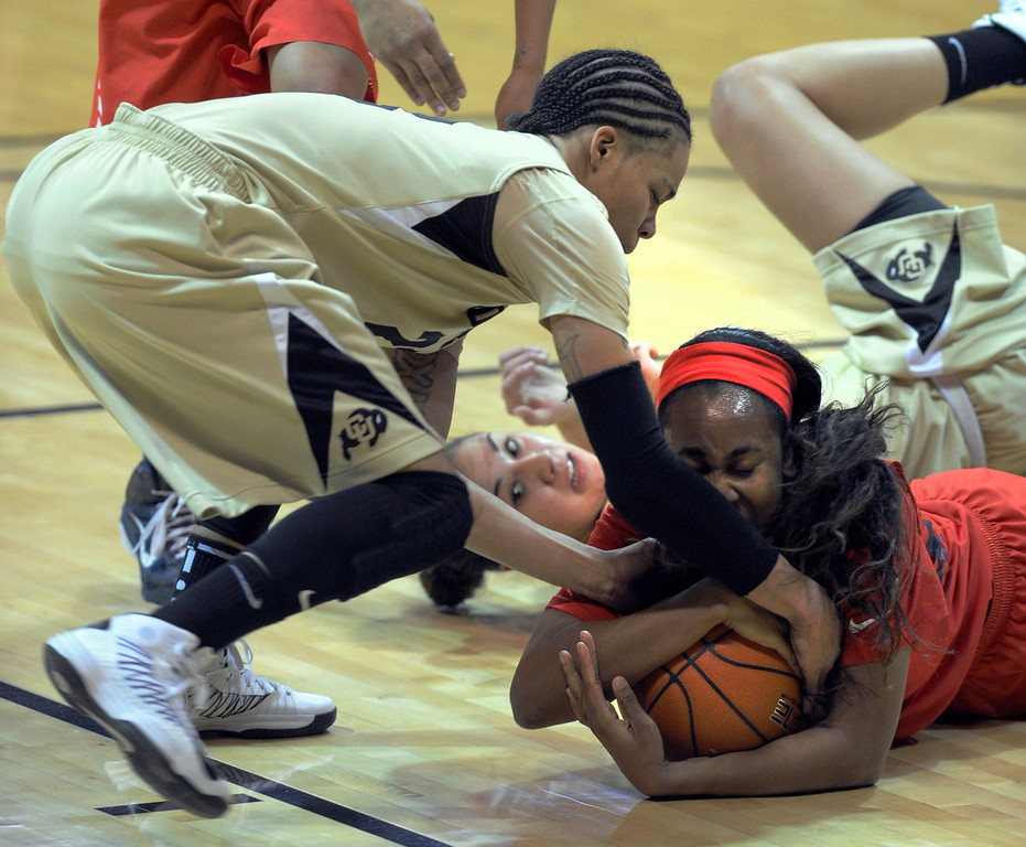 . Davellyn Whyte, right, of Arizona, tries to keep the ball from Chucky Jeffery, left, and Jasmine Sborov, both of Colorado, during the first half of the  NCAA Womens Basketball  game in Boulder Sunday Jan. 20, 2013.  Cliff Grassmick/The Daily Camera