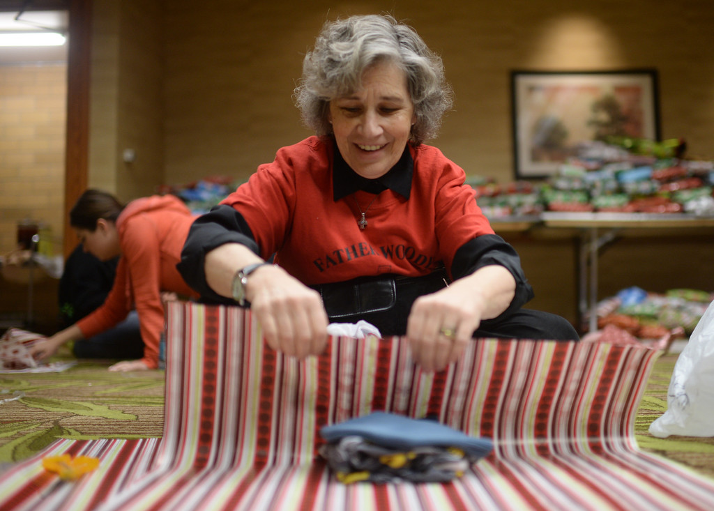 ". DENVER, CO. DECEMBER 21: Regis University  professor Victoria McCabew is wrapping Christmas gift during the annual Father Woody Christmas Party in Denver, Colorado December 21, 2013. In advance of handing out 5,000 gifts, volunteers are doing a ""wrapping party\"" at the Sheraton Denver Downtown Hotel. (Photo by Hyoung Chang/The Denver Post)"