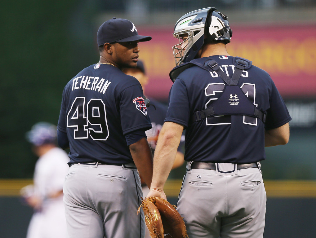 . Atlanta Braves starting pitcher Julio Teheran, left, confers with catcher Evan Gattis after Teheran gave up a double to Colorado Rockies\' Drew Stubbs in the first inning of a baseball game in Denver on Wednesday, June 11, 2014. (AP Photo/David Zalubowski)