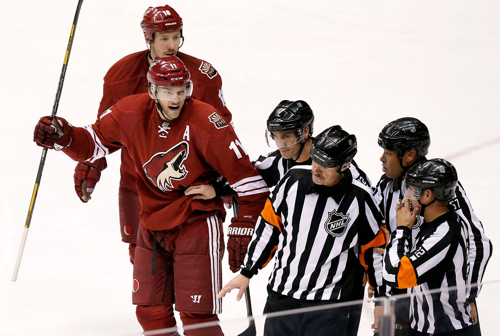 . Phoenix Coyotes\' Martin Hanzal (11), of the Czech Republic, and David Moss (18) argues with referees Ghislain Herbert (22) and Dave Jackson, third from left, and linesmen Ryan Galloway and Jay Sharrers (57) after a Coyotes goal was disallowed during the third period of an NHL hockey game against the Colorado Avalanche Thursday, Nov. 21, 2013, in Glendale, Ariz.  The Avalanche defeated the Coyotes 4-3. (AP Photo/Ross D. Franklin)