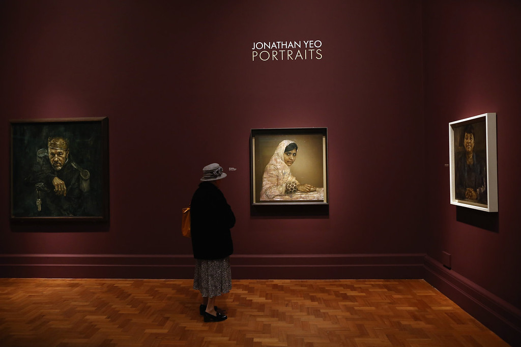 . A visitor looks at a painting of education activist  Malala Yousafzai by artist Jonathan Yeo at the National Portrait Gallery on September 10, 2013 in London, England. The exhibition of celebrity portraits includes the first painted portrait of education activist Malala Yousafzai and will run from September 10, 2013 - January 5, 2014.  (Photo by Dan Kitwood/Getty Images)