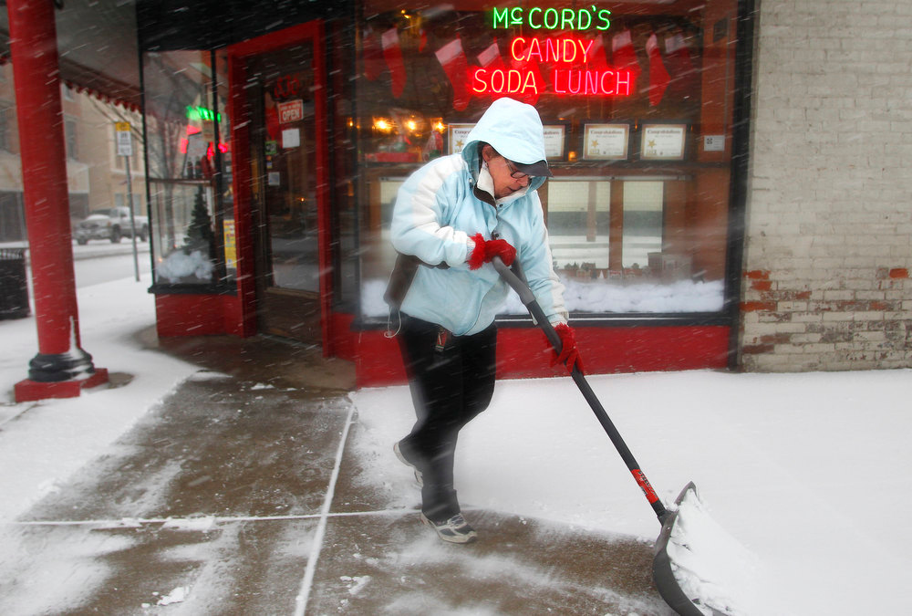 Description of . Roberta Cain shovels snow from the sidewalk outside McCord's Candies Wednesday, Dec. 26, 2012, at the corner of Sixth and Main streets in Lafayette, Ind. (AP Photo/Journal & Courier, John Terhune)