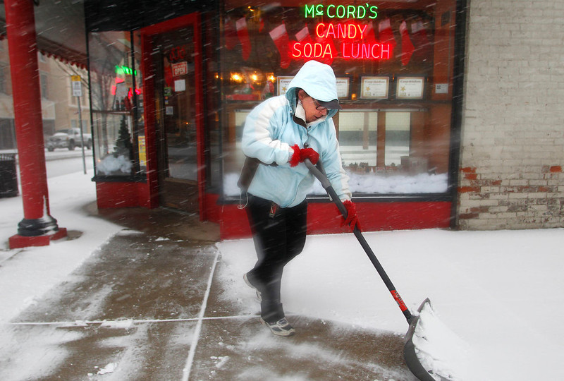 . Roberta Cain shovels snow from the sidewalk outside McCord\'s Candies Wednesday, Dec. 26, 2012, at the corner of Sixth and Main streets in Lafayette, Ind. (AP Photo/Journal & Courier, John Terhune)