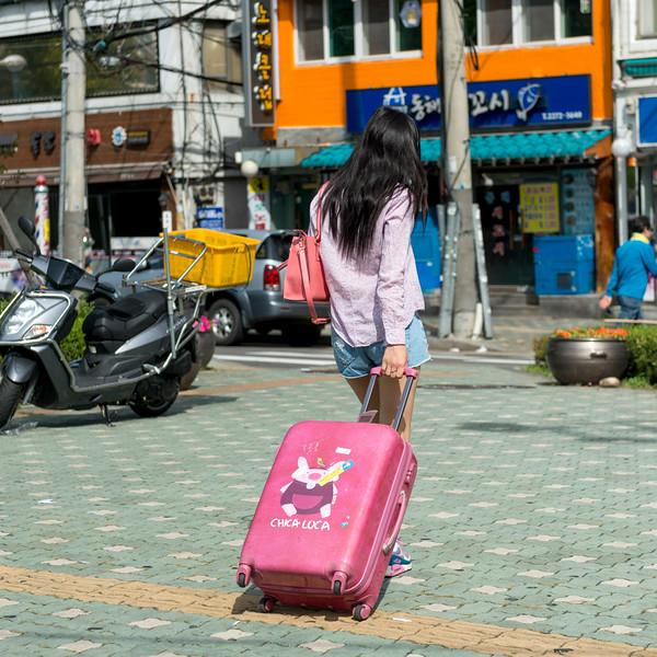 Woman with luggage at roadside, Seoul, South Korea