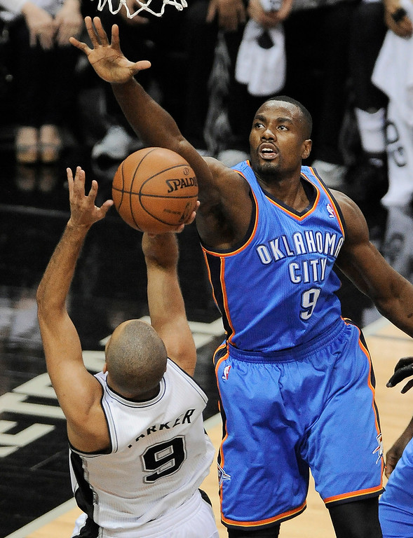 . Oklahoma City Thunder forward Serge Ibaka, right, defends San Antonio Spurs guard Tony Parker during the first half of Game 5 of the NBA basketball Western Conference finals, Thursday, May 29, 2014, in San Antonio. (AP Photo/Darren Abate)