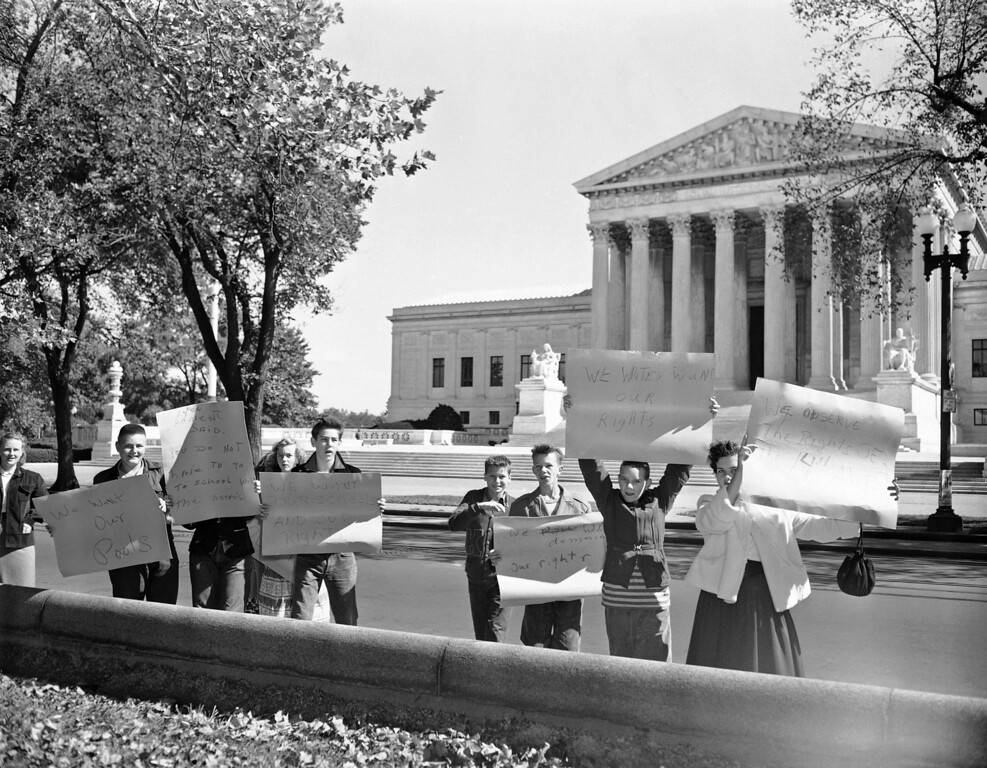 """. Children display crudely lettered signs as they pose across the street from the Supreme Court Building in Washington , Oct. 7, 1954. One sign reads: \""""We Whites want our rights\"""". The youngsters were demonstrating against attending District of Columbia schools along with black children. Until this fall white and black children had attended separate schools. (AP Photo/Henry Burroughs)"""