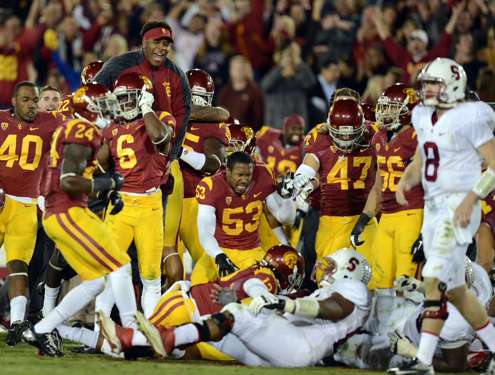 . USC players run on to the field after defeating Stanford during their game at the Los Angeles Memorial Coliseum Saturday, November 16, 2013. USC beat Stanford 20-17. (Photos by Hans Gutknecht/Los Angeles Daily News)