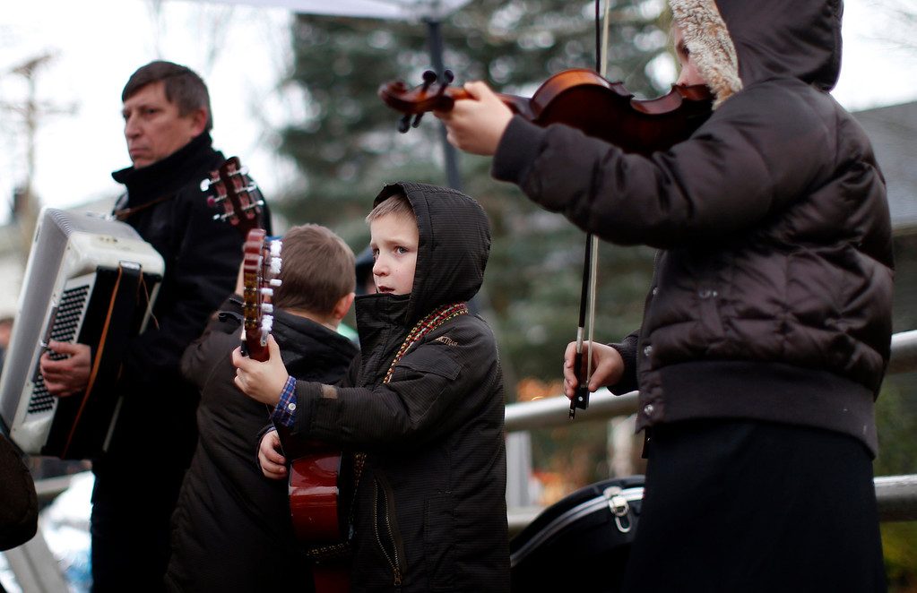 . The Kulish family from New Britain, Connecticut, plays Christmas carols near a makeshift memorial close to Sandy Hook Elementary School for the victims of a school shooting in Newtown, Connecticut Sunday December 16, 2012. Twelve girls, eight boys and six adult women were killed in the shooting on Friday at the Sandy Hook Elementary School in Newtown.  REUTERS/Mike Segar