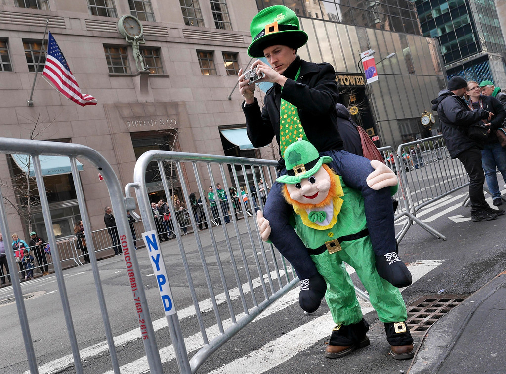 . Paul McFadden of Donegal, Ireland, seems to stand on the shoulders of a leprechaun while taking a picture before the start of the St. Patrick\'s Day Parade in New York, Tuesday, March 17, 2015. (AP Photo/Seth Wenig)