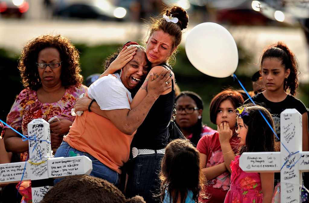 . People comfort each other at the memorial for shooting victims at the corner of E. Centerpoint Dr. and S. Sable Blvd. in Aurora, CO. Sunday, July 22, 2012.