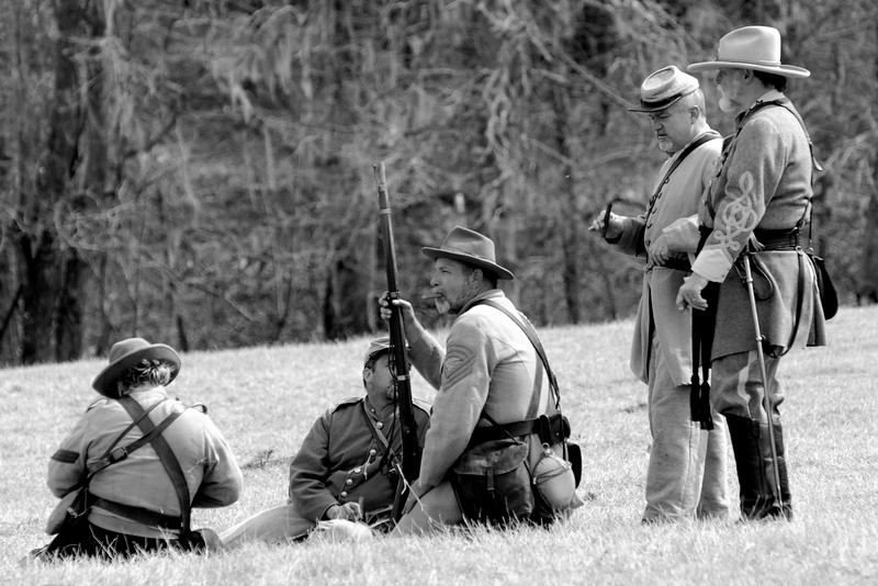 Confederate reenactors relax on the battlefield before the reenactment. The Skirmish at Gamble's Hotel happened on March 5, 1885 when 500 federal soldiers, under the command of Reuben Williams of the 12th Indiana Infantry, marched into Florence to destroy the railroad depot but were met by Confederate soldiers backed up with 400 militia. The reenactment, held by the 23rd South Carolina Infantry, was held at the Rankin Plantation in Florence, South Carolina on Saturday, March 5, 2011. Photo Copyright 2011 Jason Barnette