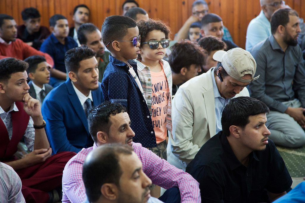 . Children stand among men during a prayer service at Masjid Al-Farooq for the Muslim holiday of Eid al-Fitr, Friday, June 15, 2018, in the Brooklyn borough of New York. They join hundreds of millions of Muslims around the world in marking the holiday that caps the fasting month of Ramadan. (AP Photo/Mark Lennihan)