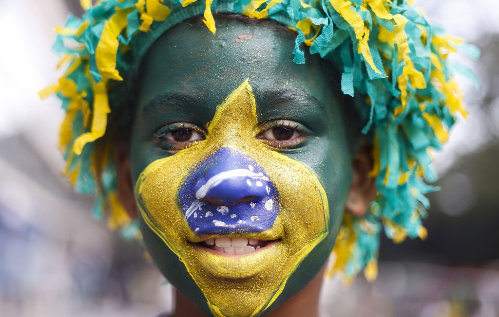 . Brazil\'s supporters pose as they gather to watch the 2014 FIFA World Cup Brazil vs Mexico match at the FIFA Fan Fest public viewing event in Sao Paulo, Brazil on June 17, 2014. AFP PHOTO/Miguel Schincariol/AFP/Getty Images