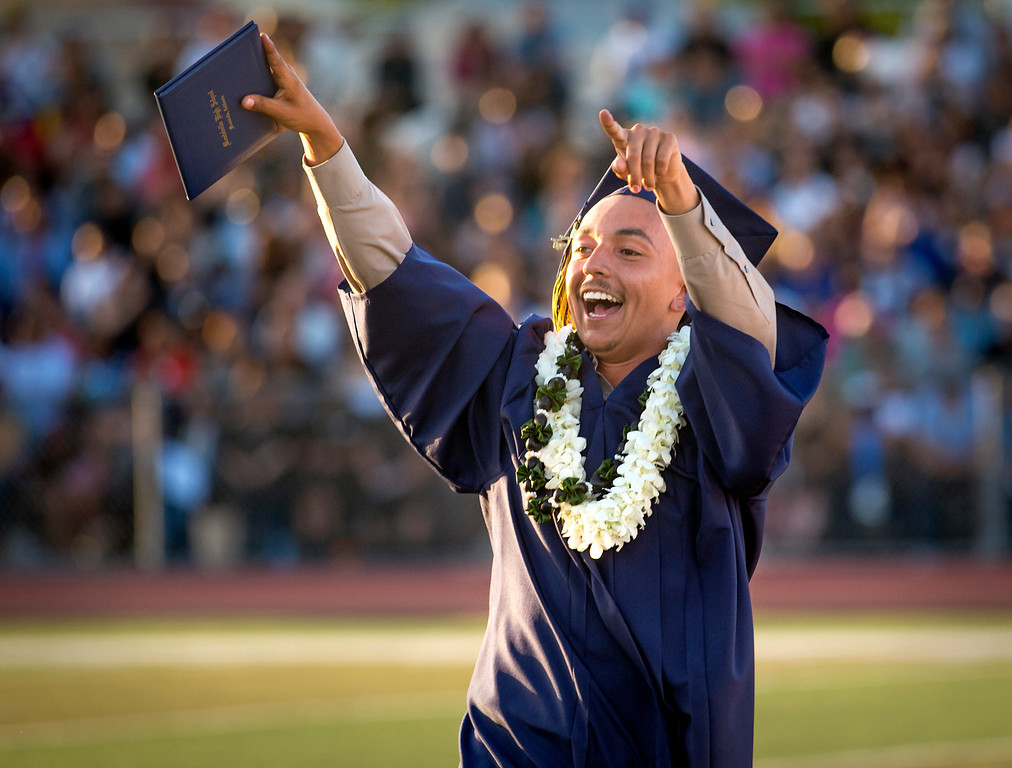 . Montebello High graduate Geoffrey Sobarzo waves to friends and family in the stands during commencement June 19, 2014.  (Staff photo by Leo Jarzomb/Whittier Daily News)