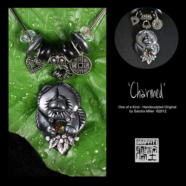 """CHARMED-  CLICK HERE TO VIEW VIDEO DESCRIPTION IN A NEW WINDOW  This little lady has really got it all going on, from the beautiful Swarovski crystal that she has holding between paws, all the way up to the delicious charms hanging from the gunmetal chain above.  The adorable  chow was sculpted in polymer clay then fired to a durable hardness. Then multiple coats of a gunmetal finish were applied and a high gloss polymer resin coat added for a permanent finish  The Crystal she's holding is like a little fireball  and it is from the 1940s.  It  has tiny facets all over and looks much like a mini disco ball…tons of fire and ice!!  PENDANT MEASURES   2 3/4 x 2"""" High quality caprice snake chain is adjustable from 16-20"""" long  Beads may be changed or removed by unscrewing end"""