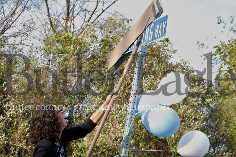 Slippery Rock parks director Mary Messer reveals the new Manning Way sign at a dedication ceremony Tuesday. Seb Foltz/Butler Eagle