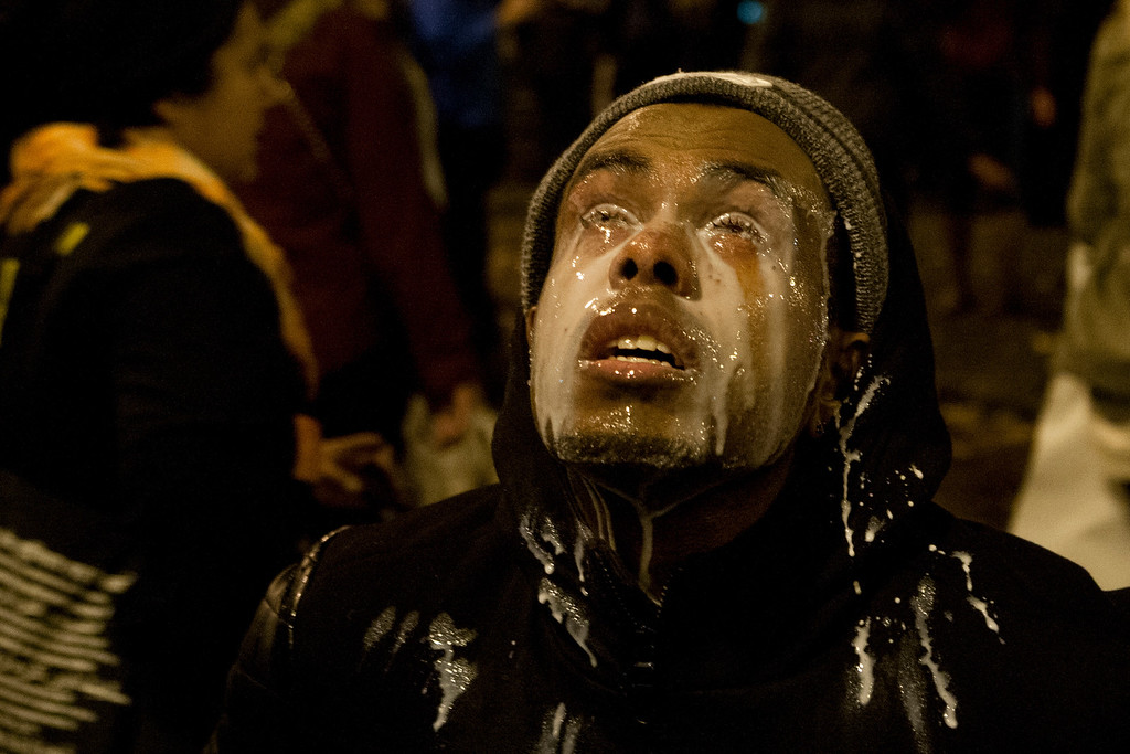 . A protestor pours milk in his eyes after being tear gassed by Seattle police at the Interstate 5 entrance on Cherry Street in Seattle, Monday, Nov. 24, 2014. Protestors took to the streets in response to the Ferguson, Mo., grand jury decision not to indict Officer Darren Wilson in the death of Michael Brown. (AP Photo/seattlepi.com, Anna Erickson)