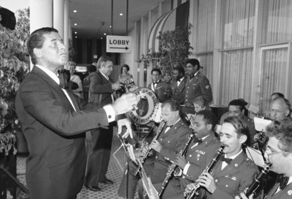 . Entertainer Jerry Lewis, left, performs with the United States Army Reserve Band at the Beverly Hilton Hotel Hills prior to his receipt of the Department of Defense Medal for Distinguished Service, Saturday, June 8, 1985, Beverly Hills, Calif. Lewis was honored with the militarys highest civilian award for to the eradication of Muscular Dystrophy and related diseases. (AP Photo/Michael Tweed)