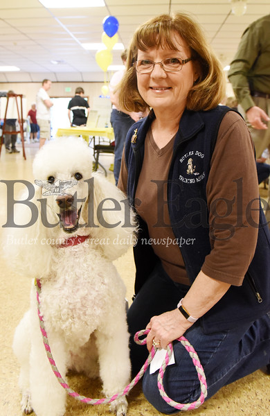 Harold Aughton/Butler Eagle: Cheryl Youkers of Butler brought her 12-year-old, standard poodle, and therapy dog, Tuil, to the pet blessing held at the Butler Vagabonds Sunday afternoon.