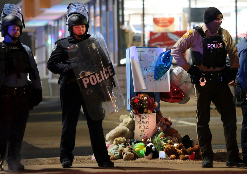 . Police guard the entrance to a gas station in front of a memorial to Antonio Martin on Wednesday, Dec. 24, 2014, in Berkeley, Mo. The mayor of the St. Louis suburb of Berkeley urged calm Wednesday after a white police officer killed the black 18-year-old who police said pointed a gun at him, reigniting tensions that have lingered since the death of Michael Brown in neighboring Ferguson. (AP Photo/St. Louis Post-Dispatch, Robert Cohen)