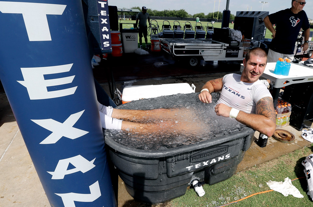 . Houston Texans tight end C.J. Fiedorowicz sits in a tub of ice water after an NFL football training camp practice on Saturday, July 26, 2014, in Houston. (AP Photo/David J. Phillip)